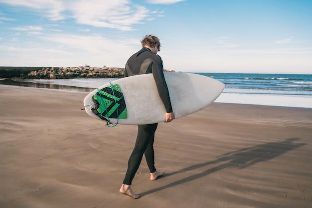 若いサーファーが黒いサーフィンスーツで彼のサーフボードを海に立っています。スポーツとウォータースポーツのコンセプトです。 無料写真