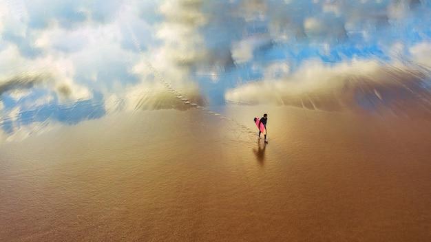 砂浜を歩く若いサーファー 無料写真