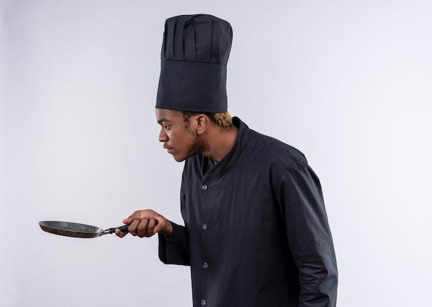 Il giovane cuoco afroamericano sorpreso in uniforme dello chef si leva in piedi lateralmente e guarda la padella isolata sul muro bianco Foto Gratuite