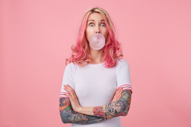 Young surprised beautiful pink haired woman with tattooed hands, wears in white t-shirt, blows gum ball, looking to the left in surprise, stands. Free Photo