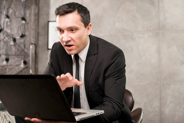 Young surprised businessman browsing laptop at home Free Photo