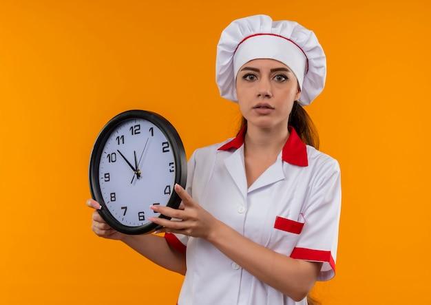 La giovane ragazza caucasica sorpresa del cuoco in uniforme del cuoco unico tiene l'orologio isolato sulla parete arancione con lo spazio della copia Foto Gratuite