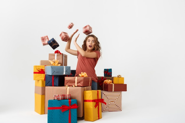 Young surprised curly woman among lying and falling gift boxes Free Photo