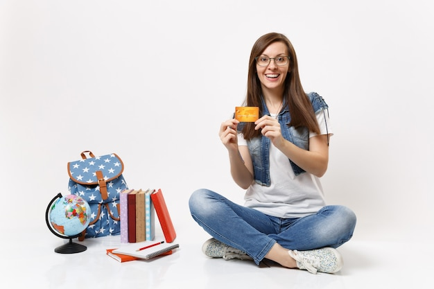 Young surprised joyful woman student in glasses denim clothes holding credit card sitting near globe backpack, school books isolated Free Photo