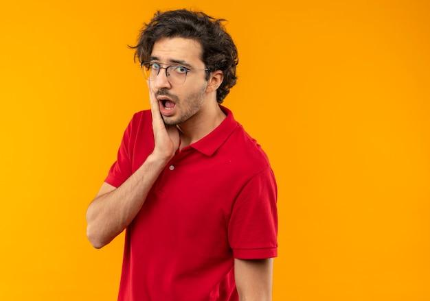 光学メガネと赤いシャツを着た若い驚きの男は顔に手を置き、オレンジ色の壁に孤立して見える 無料写真