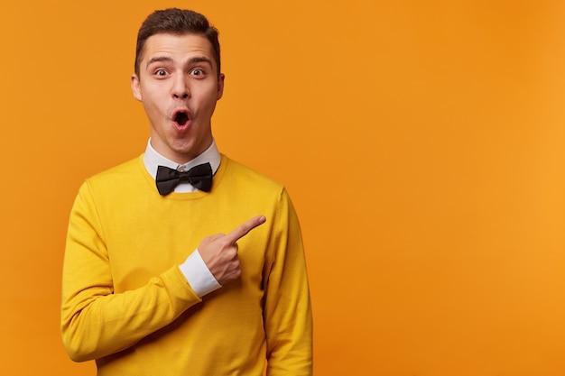 Молодой удивленный мужчина в желтом свитере, белой рубашке и черном галстуке-бабочке, указывая пальцем вправо, кричит «вау» Бесплатные Фотографии