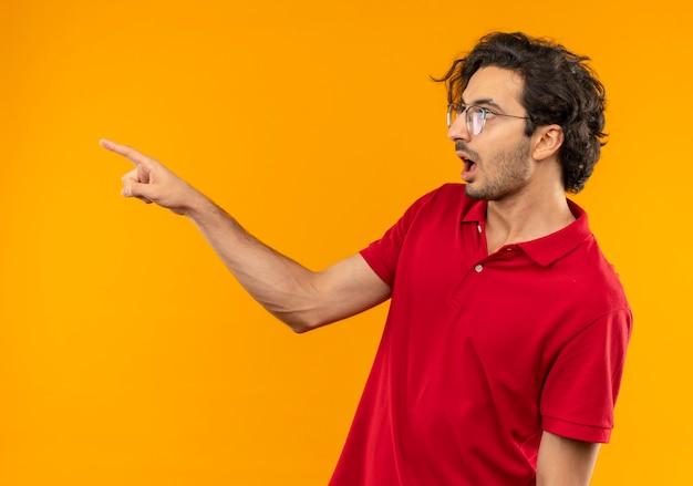 Giovane uomo sorpreso in camicia rossa con vetri ottici si leva in piedi lateralmente e punta a lato isolato sulla parete arancione Foto Gratuite