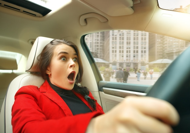 Giovane donna sorpresa alla guida di un'auto Foto Gratuite