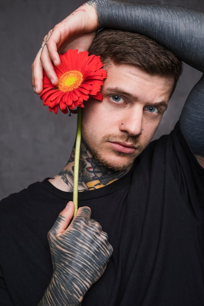 Young tattooed man with piercing in his nose holding flower near his ears looking to camera Free Photo