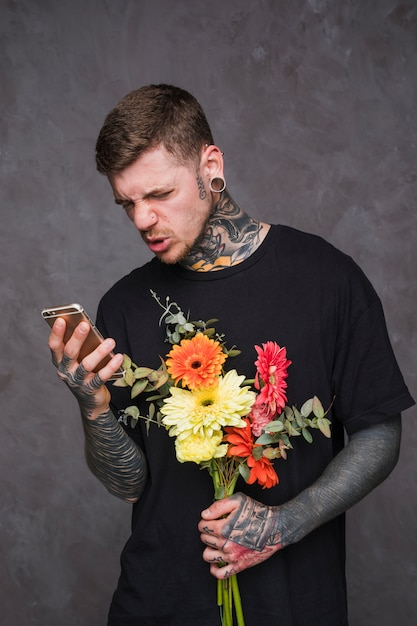 Young tattooed and pierced man holding flower bouquet in hand making face while using mobile phone Free Photo
