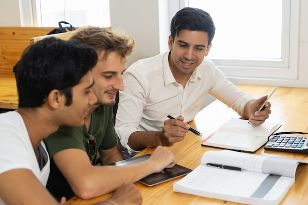Young teacher telling two students about corporate budgeting Free Photo