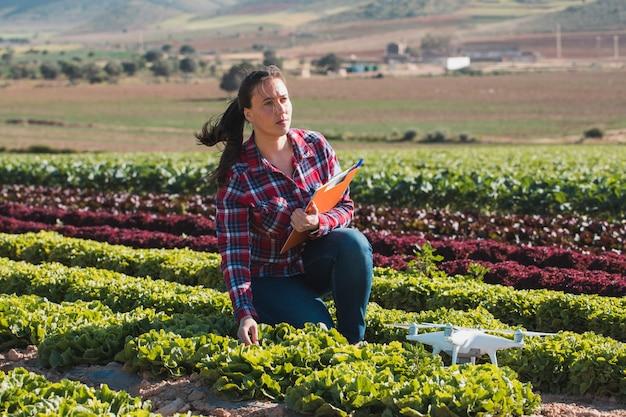 Молодая техническая женщина, работающая в области салатов с папкой и гул Premium Фотографии