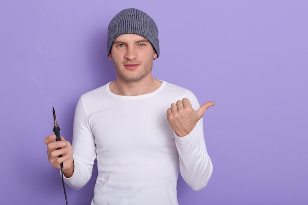 Young technician being ready to solder wire, attractive male wears white casual shirt and gray cap holds soldering iron in one hand and point aside with another thumb, isolated on purple. Free Photo