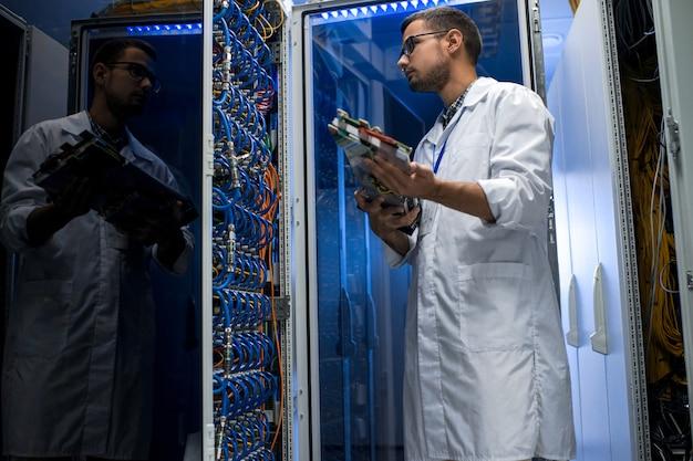 Молодой техник работает с суперкомпьютером Premium Фотографии