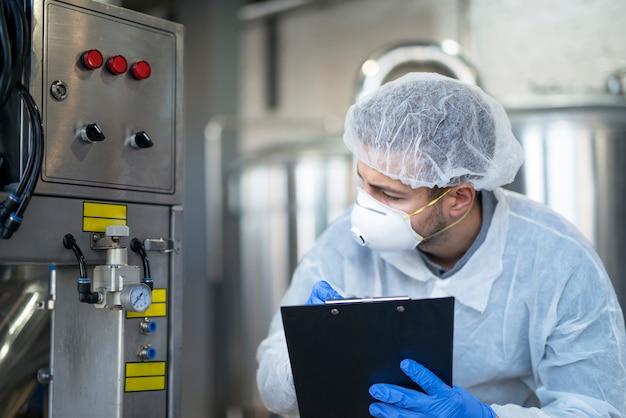Giovane tecnologo in uniforme protettiva bianca che controlla la macchina industriale presso l'impianto di produzione Foto Gratuite