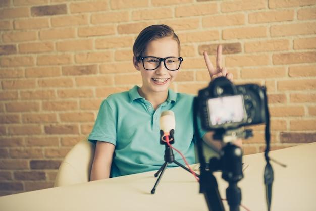 Молодой мальчик-подросток-блоггер настраивает камеру для записи домашнего видеоурока видеоблога. ит-блог или видеоблог, трансляция в социальных сетях или концепция онлайн-курса обучения Premium Фотографии