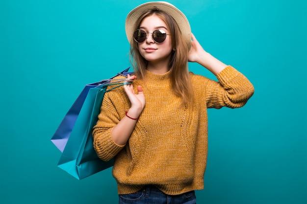 Giovane donna teenager in occhiali da sole e cappello che tiene i sacchetti della spesa nelle sue mani sentirsi così felicità isolato sulla parete verde Foto Gratuite