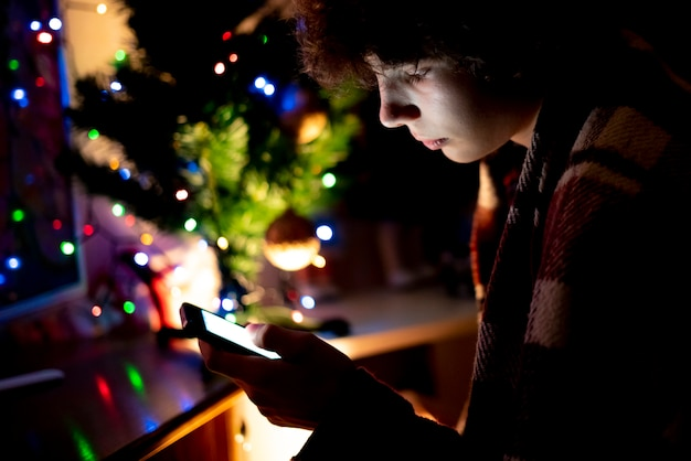 Young teenage boy using the smartphone on the christmas night at home near the tree. Premium Photo