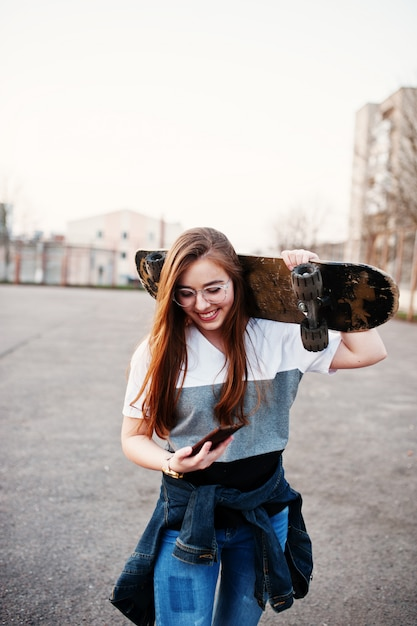 Young teenage urban girl with skateboard, wear on glasses, cap and ripped jeans at the yard sports ground on sunset making selfie on phone. Premium Photo