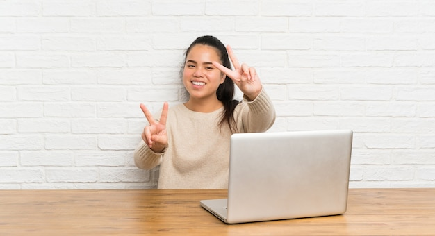 Young teenager asian girl with a laptop in a table smiling and showing victory sign Premium Photo