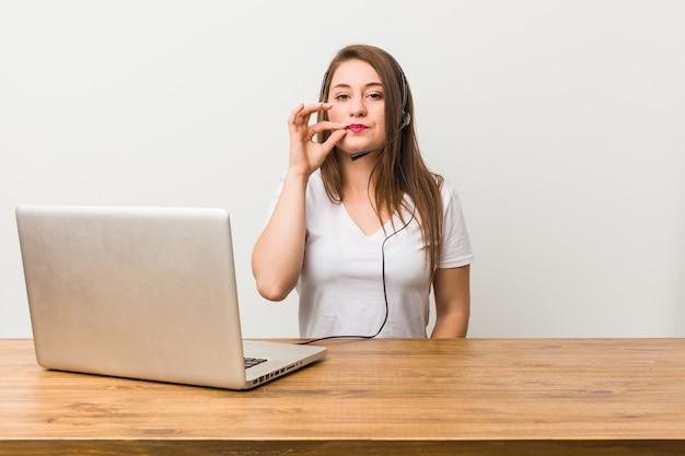 秘密を守る唇に指で若いテレマーケティング女性。 Premium写真