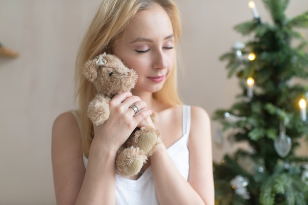 Young tender girl in nightie hugs toy bear with christmas tree on background. Premium Photo