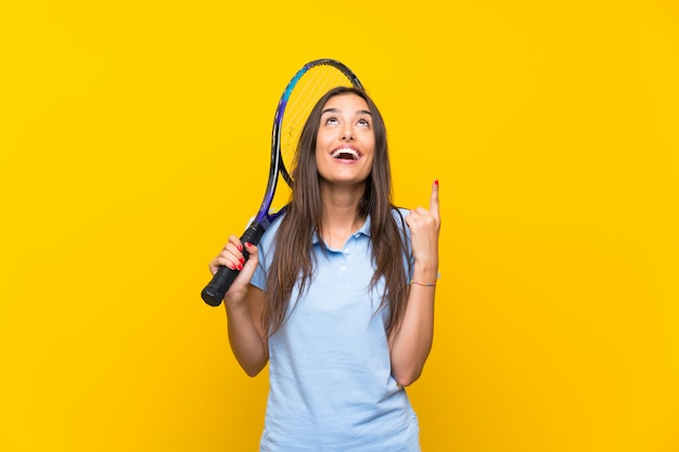 Young tennis player woman over isolated yellow wall pointing up a great idea Premium Photo