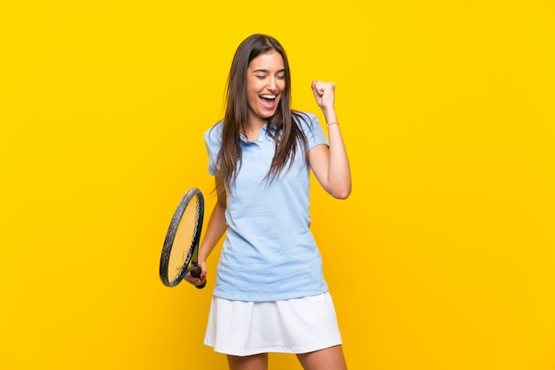 Young tennis player woman over isolated yellow wall Premium Photo
