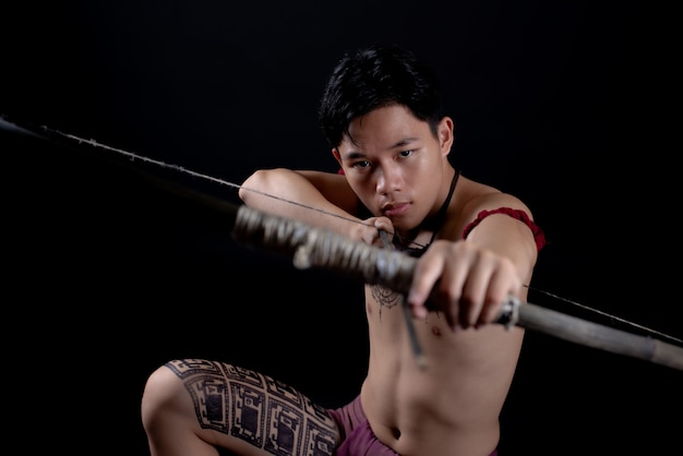 Young thailand male warrior posing in a fighting stance with a bow Free Photo