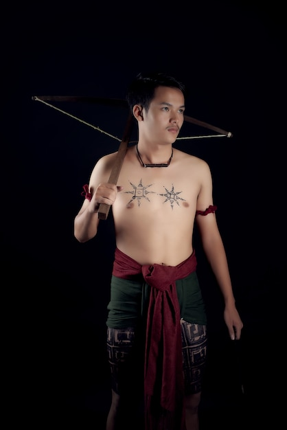 Young thailand male warrior posing in a fighting stance with a crossbow Free Photo