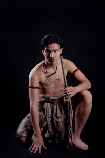 Young thailand male warrior posing in a fighting stance with a sword Free Photo