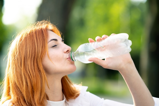 Young thirsty redhead woman drinking water from a bottle in summer park. Premium Photo