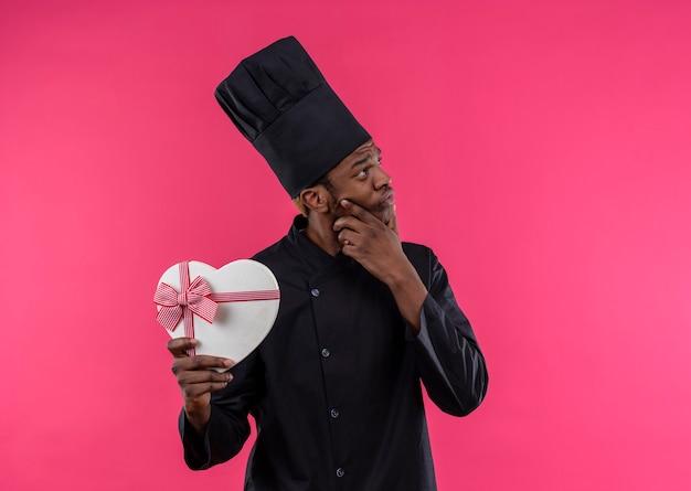 シェフの制服を着た若い思慮深いアフリカ系アメリカ人の料理人は、ピンクの壁に分離されたハート型ボックスを保持します 無料写真