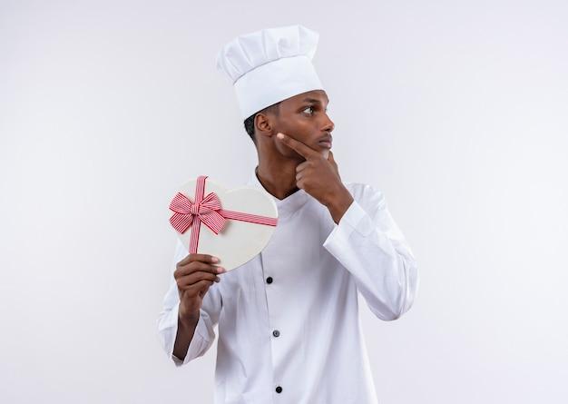 シェフの制服を着た若い思慮深いアフリカ系アメリカ人の料理人は、ハート型の箱を保持し、白い壁に隔離されたあごに手を置きます 無料写真