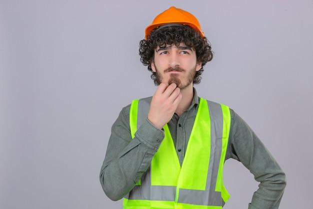 Молодой вдумчивый панированный красивый инженер-рабочий, стоящий с озадаченным взглядом, почесывая подбородок, думает на изолированном белом фоне Бесплатные Фотографии
