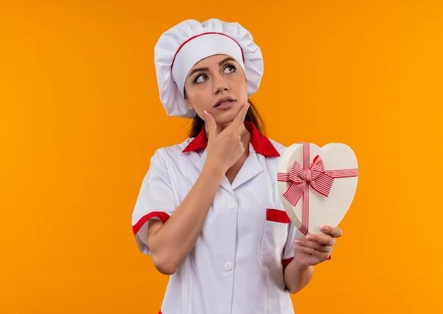 シェフの制服を着た若い思慮深い白人料理人の女の子は、ハート型ボックスを保持し、コピースペースでオレンジ色の壁に分離されたあごに手を置きます 無料写真
