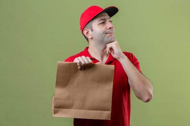 고립 된 녹색 배경 위에 의아해 턱에 손으로 제쳐두고 찾고 종이 패키지를 들고 빨간색 유니폼을 입고 젊은 사려 깊은 배달 남자 무료 사진