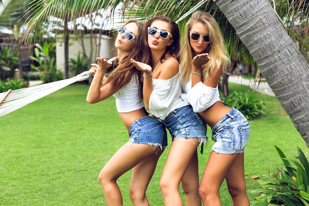 公園でポーズをとって、夏の時間に楽しんでいる若い3人の幸せな美しい女の子 無料写真