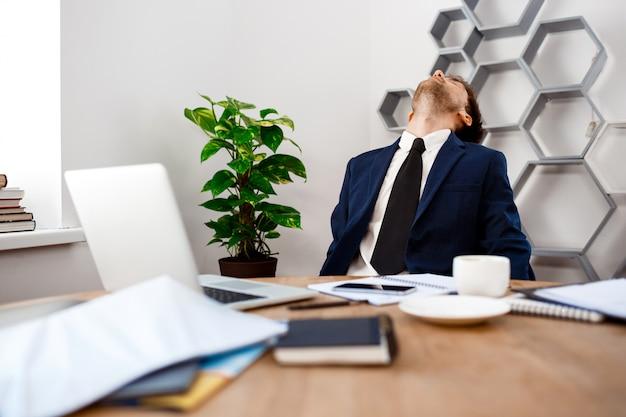 Giovane uomo d'affari stanco che si siede nel luogo di lavoro, fondo dell'ufficio. Foto Gratuite
