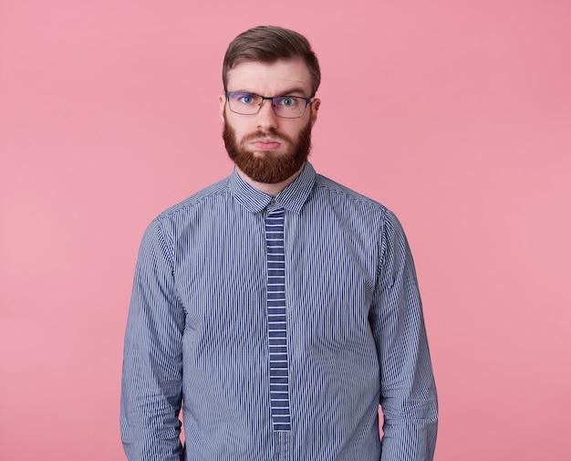 Молодой уставший от работы рыжебородый парень в очках и полосатой рубашке смотрит вдаль, думает, сколько еще проектов закрыть и успеет ли он, изолировавшись на розовом фоне. Бесплатные Фотографии