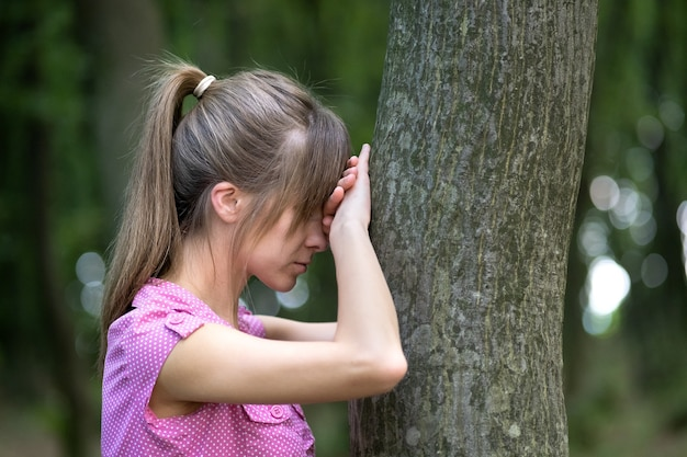 Молодая усталая женщина, склоняющаяся к стволу дерева в летнем лесу. Premium Фотографии