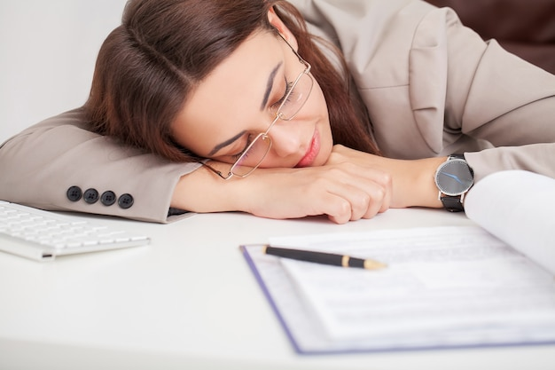Young tired woman at office desk sleeping with eyes closed, sleep deprivation and stressful life concept Premium Photo