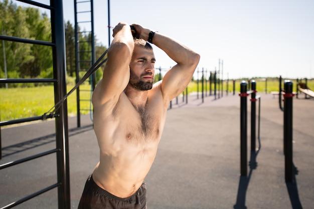 スポーツ施設で運動しながら抵抗バンドを保持し、ストレッチする若いトップレススポーツマン Premium写真