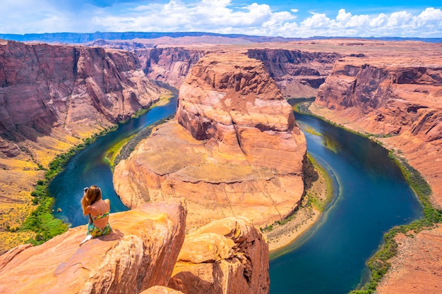 Young tourist girl with green dress at horseshoe bend taking a picture, arizona. united states Premium Photo