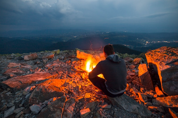 Young tourist man sitting on summer night at bright fire on rocky mountain top under cloudy sky. Premium Photo