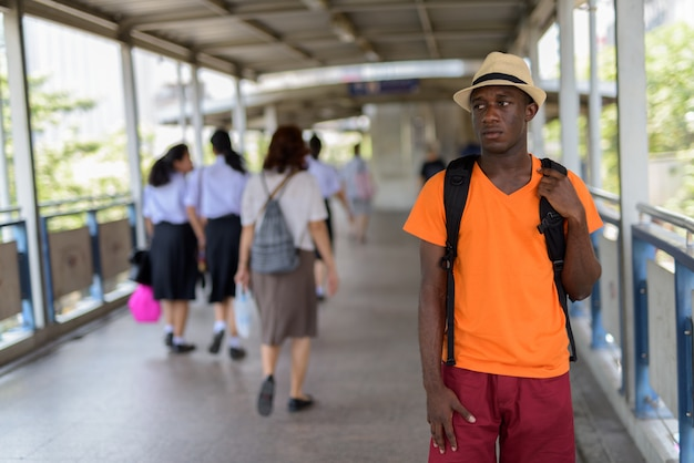 Young tourist man standing and thinking at the footbridge of subway station in bangkok thailand Premium Photo