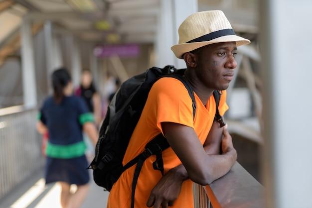 Young tourist man thinking while looking away at the footbridge of subway station in bangkok thailand Premium Photo