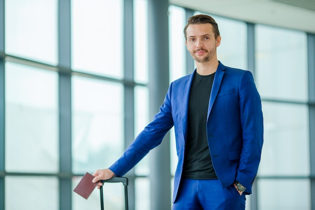 旅行の準備ができて空港でパスポートと搭乗券を持つ若い観光客男 Premium写真
