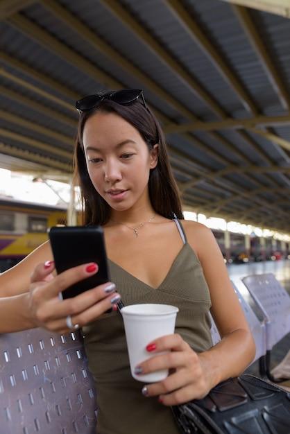 Молодая туристическая женщина пьет кофе и пользуется мобильным телефоном Premium Фотографии