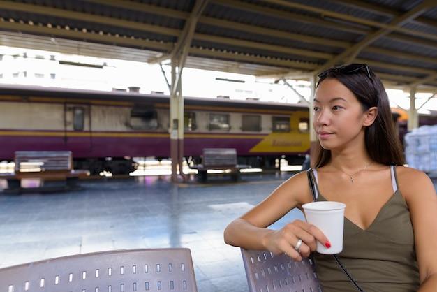 Молодая туристическая женщина, имеющая перерыв на кофе на вокзале Premium Фотографии